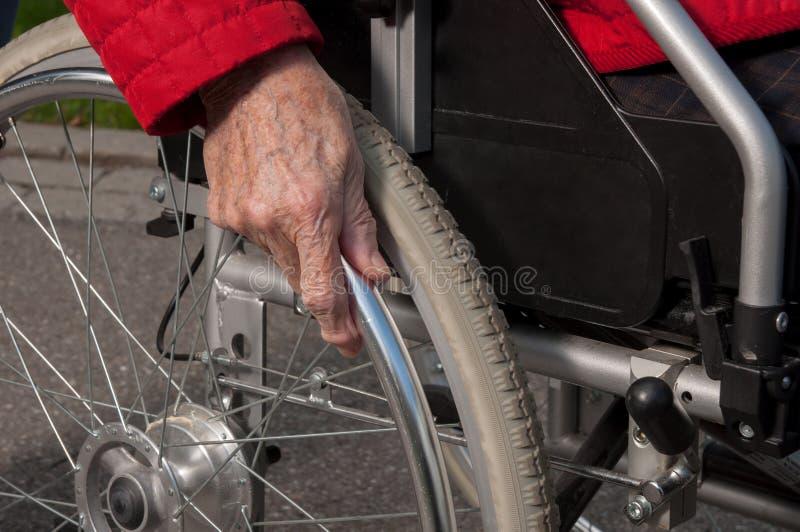 Hög kvinnahand på rullstolen royaltyfri fotografi