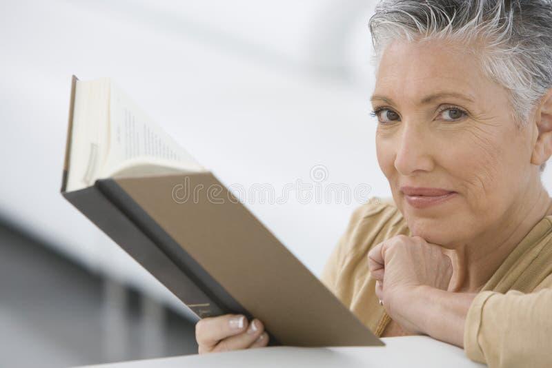 Hög kvinnaläsebok på soffan royaltyfria foton