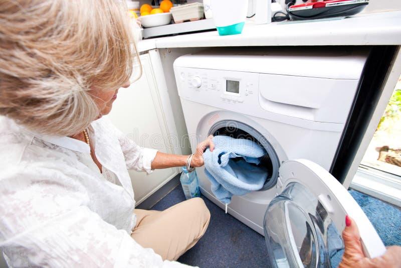 Hög kvinnapäfyllningshandduk i tvagningmaskin hemma arkivfoto