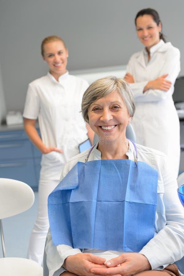 Hög kvinnapatient med det yrkesmässiga tandläkarelaget royaltyfria bilder