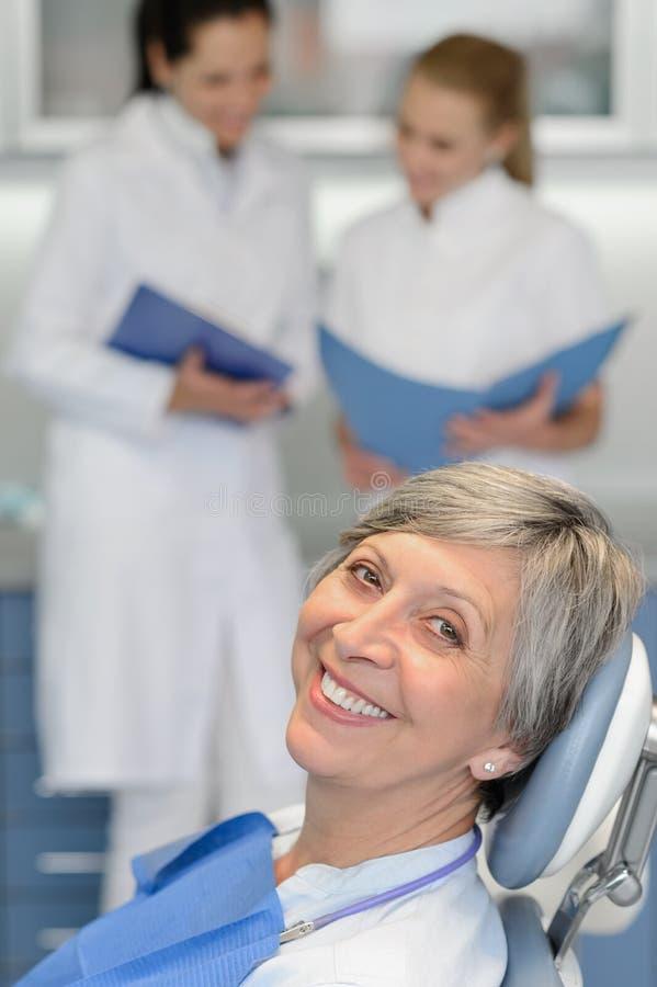 Hög kvinnapatient på att le för tandläkarekirurgi arkivfoto