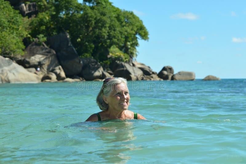 Hög kvinnasimning i havet arkivfoto