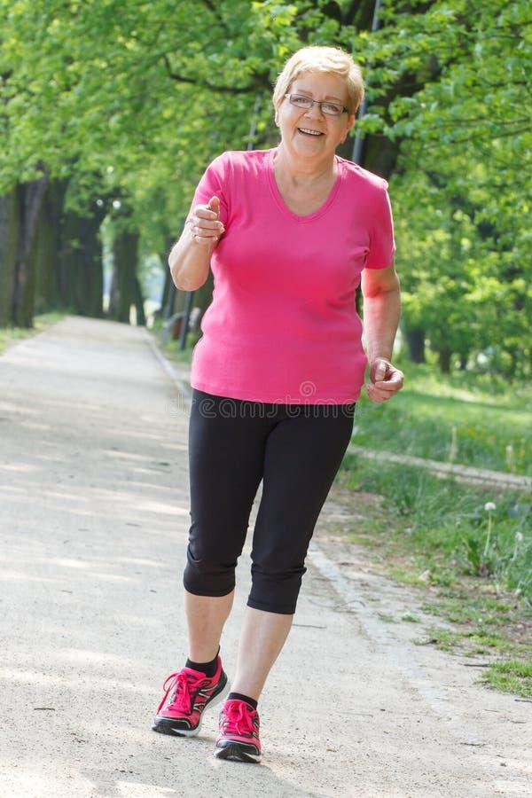 Hög kvinnaspring i soligt parkerar och att jogga utanför, den sunda livsstilen arkivbilder