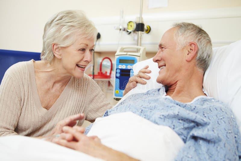 Hög kvinnlig besöka make i sjukhussäng royaltyfri bild