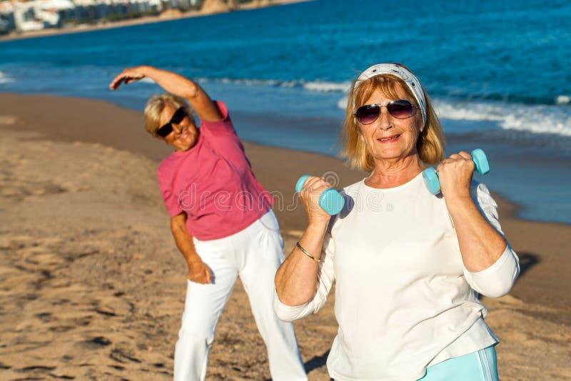 Hög kvinnlig konditionperiod på stranden. royaltyfri bild