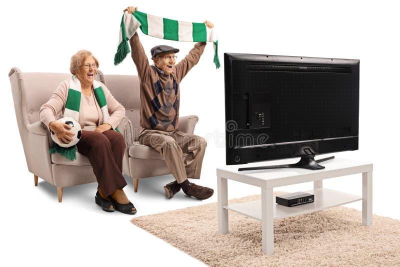 Hög kvinnlig och manliga fotbollfans som hurrar med en halsduk och håller ögonen på en lek royaltyfria bilder