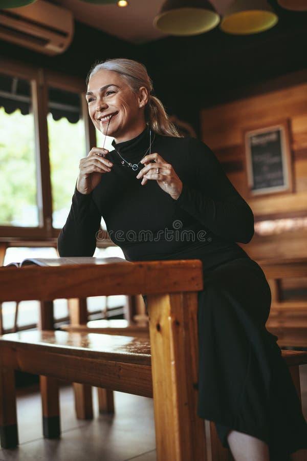 Hög kvinnlig på kafét som bort ser och ler arkivbilder