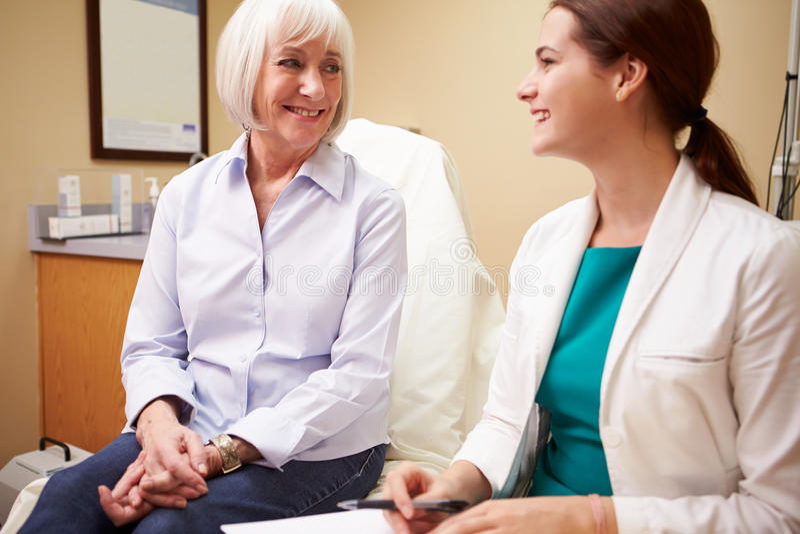 Hög kvinnlig patient för doktor In Consultation With royaltyfri foto