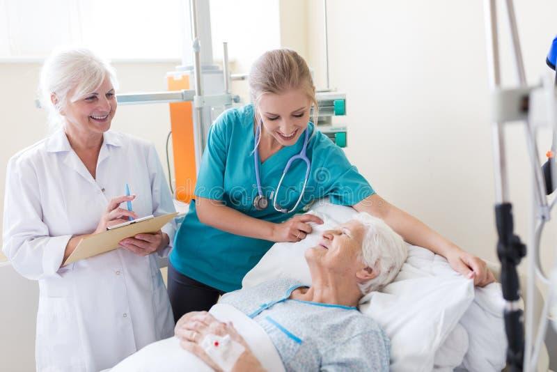 Hög kvinnlig patient i sjukhussäng arkivfoton