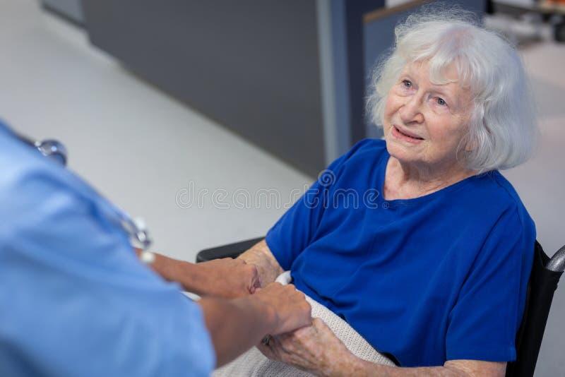 Hög kvinnlig patient som rymmer händer av kirurgen i sjukhuskorridor arkivfoton