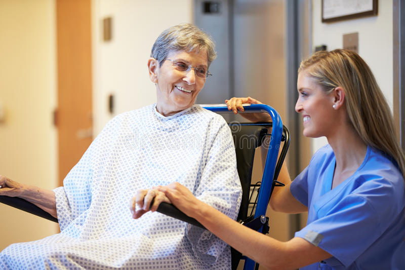 Hög kvinnlig patient som skjuts i rullstol av sjuksköterskan royaltyfri fotografi