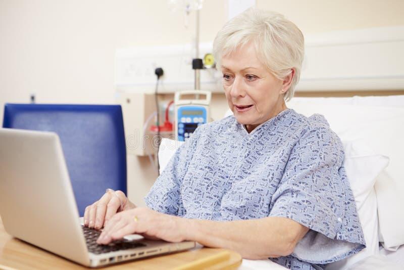 Hög kvinnlig tålmodig användande bärbar dator i sjukhussäng arkivfoto