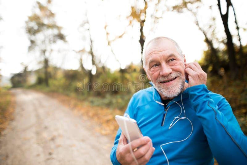 Hög löpare i natur med den smarta telefonen med hörlurar arkivfoto