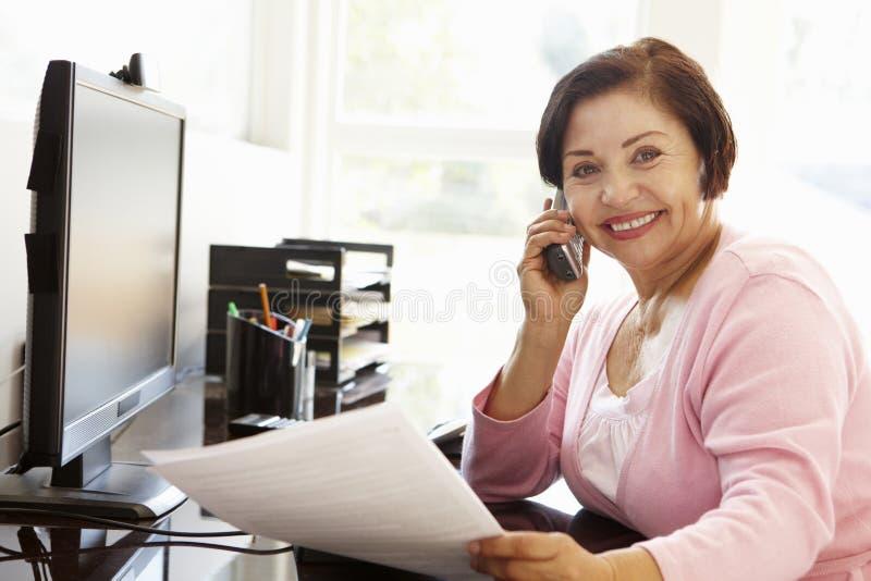 Hög latinamerikansk kvinna som hemma arbetar på datoren arkivfoto