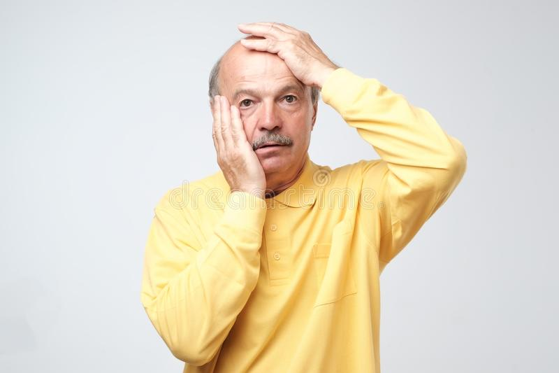 Hög latinamerikansk man i den gula tshirten som drar hud på framsida med händer Han skrämmas eller tröttas av spänning arkivfoto