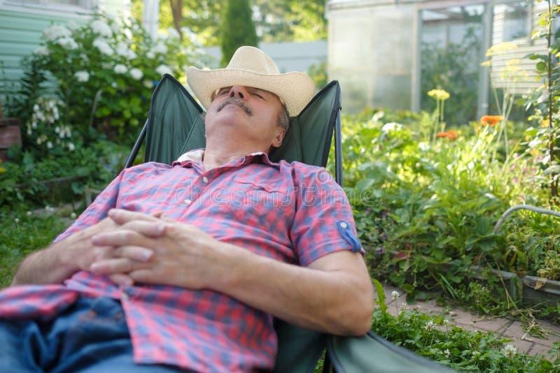 Hög latinamerikansk man i sittande luta för hatt tillbaka på stol som sover i utomhus- sommarblommaträdgård fotografering för bildbyråer
