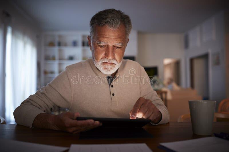 Hög latinamerikansk man som sitter på en tabell som hemma läser en e-bok i aftonen, slut upp arkivfoton