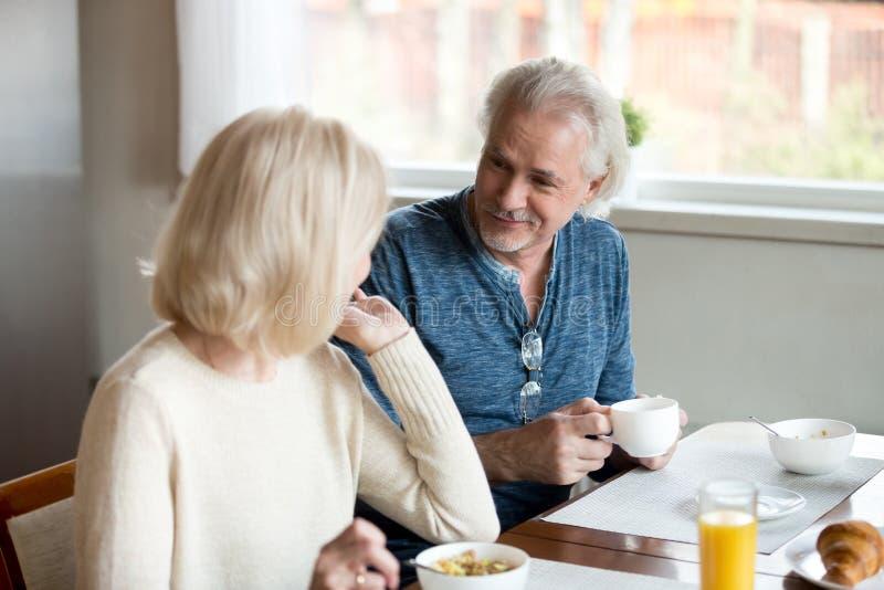 Hög makeblick på frun som tycker om frukosten i kök royaltyfri fotografi
