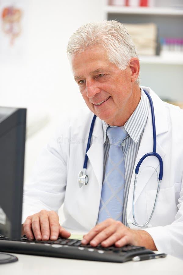 Hög male doktor på skrivbordet arkivfoto