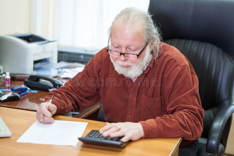 Hög man för matematiker som beräknar och skriver på tabellen på arbetsplatsen, manligt sammanträde i stol royaltyfri bild