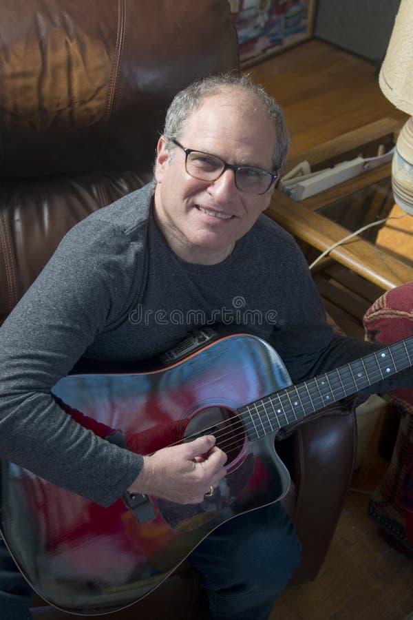 Hög man för mellersta ålder som spelar den akustiska gitarren royaltyfria bilder