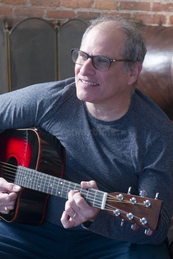 Hög man för mellersta ålder som spelar gitarren arkivfoto