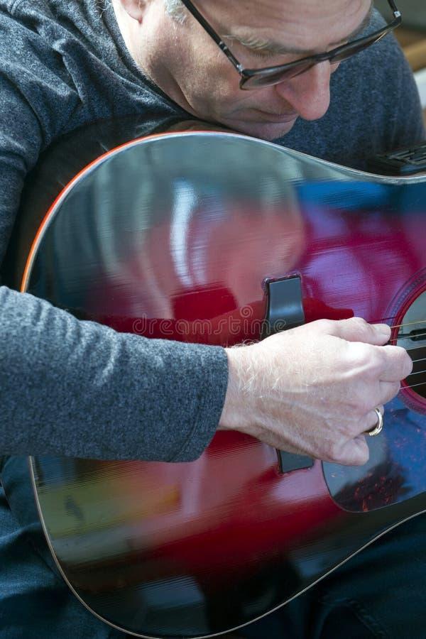 Hög man för mellersta ålder som spelar gitarren arkivfoton