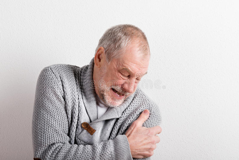 Hög man i den gråa woolen tröjan, studioskott fotografering för bildbyråer