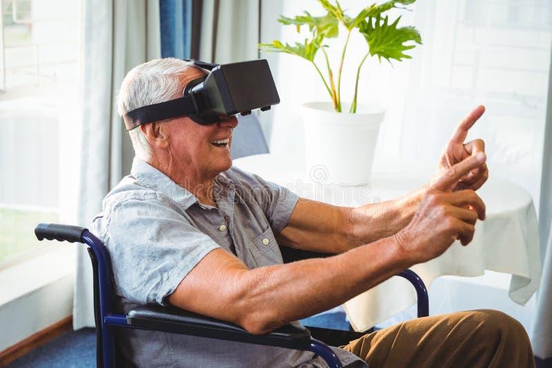 Hög man i en rullstol genom att använda en virtuell verklighetapparat royaltyfria foton