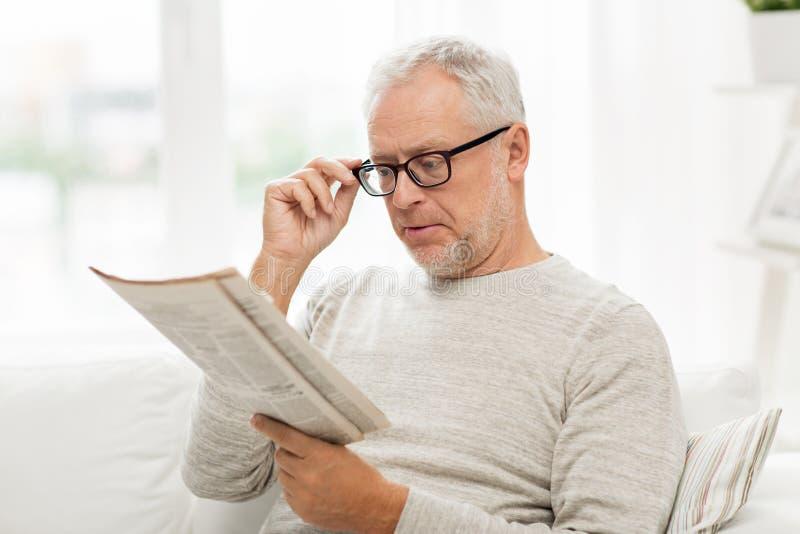 Hög man i exponeringsglas som hemma läser tidningen royaltyfria foton