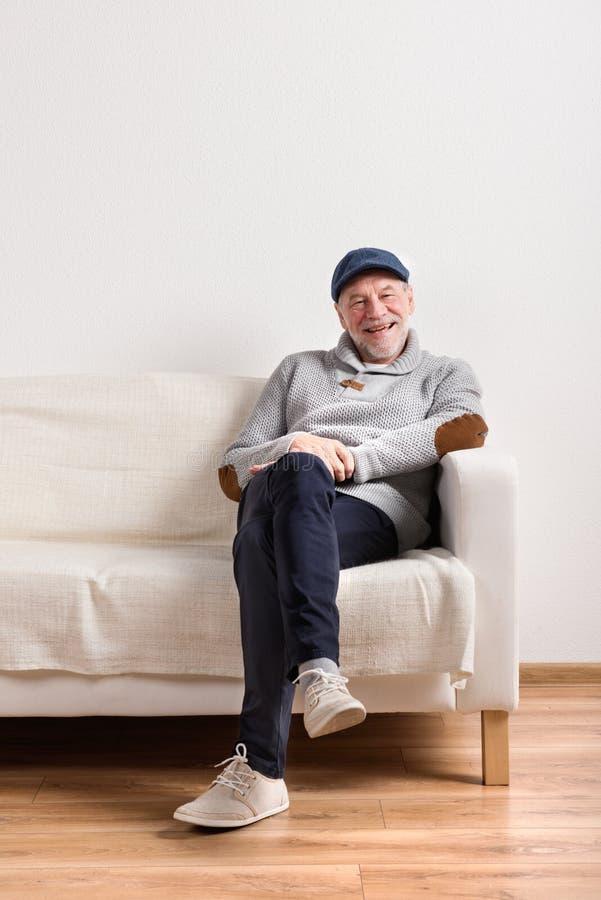 Hög man i grått tröjasammanträde på soffan, studioskott royaltyfri foto