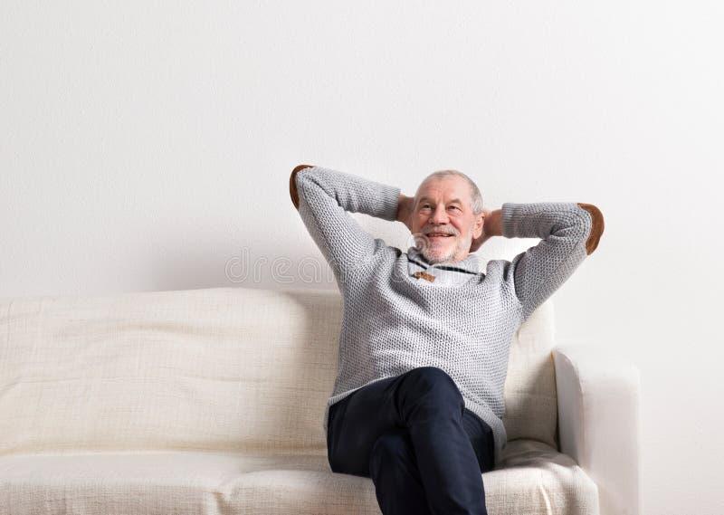 Hög man i grått tröjasammanträde på soffan, studioskott arkivfoto