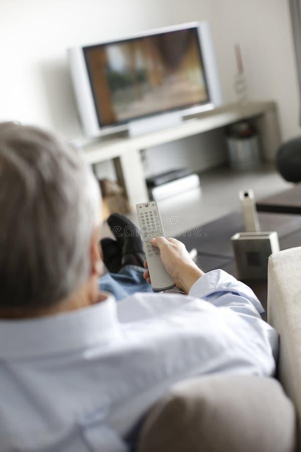Hög man i hållande ögonen på tv för soffa fotografering för bildbyråer