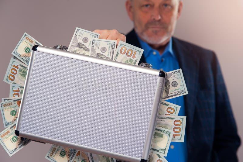 Hög man i hållande fall för dräkt med dollarräkningar royaltyfri bild