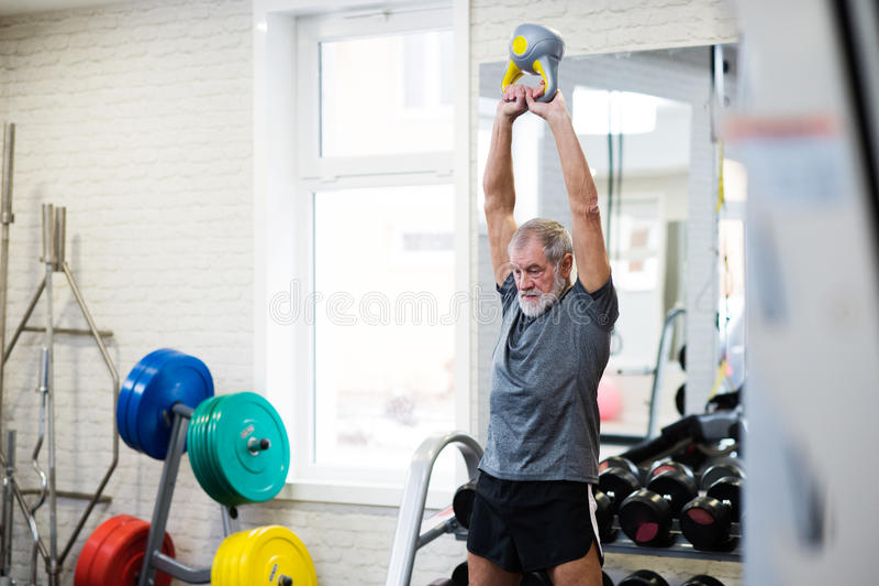 Hög man i idrottshall som utarbetar genom att använda kettlebells royaltyfri bild