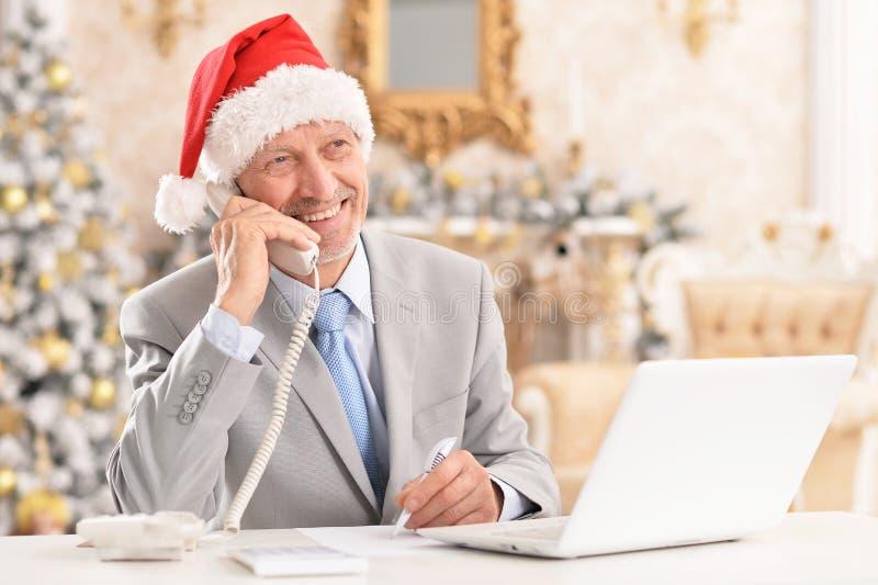 Hög man i jultomtenhattarbete med bärbara datorn hemma arkivbilder