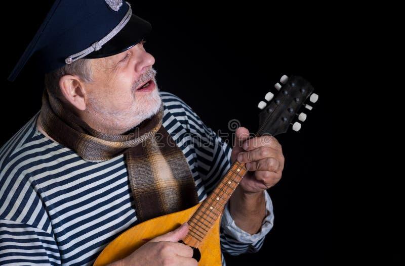 Hög man i randig väst och napp med mandolinen arkivfoto