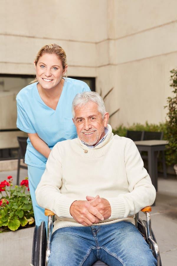 Hög man i rullstol och geriatrisk sjuksköterska arkivfoton