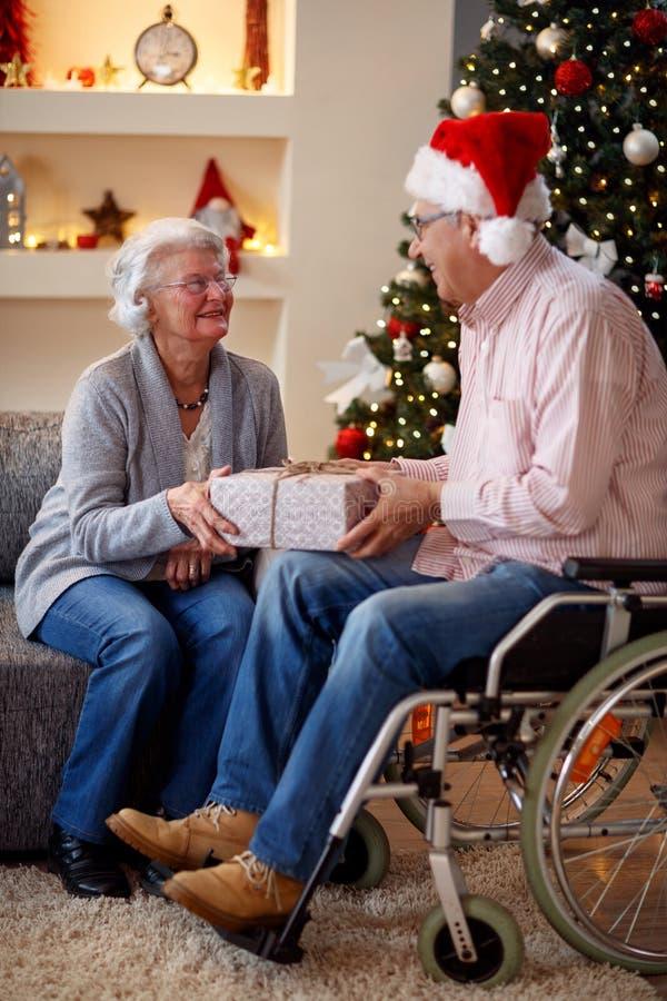 Hög man i rullstol och kvinna med julgåvan royaltyfria foton