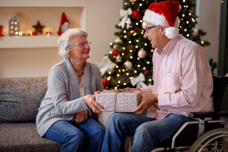 Hög man i rullstol och lekvinna med julgåvan fotografering för bildbyråer
