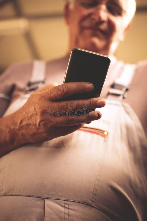 Hög man i seminarium Hållande mobil för man och läs- text royaltyfri bild