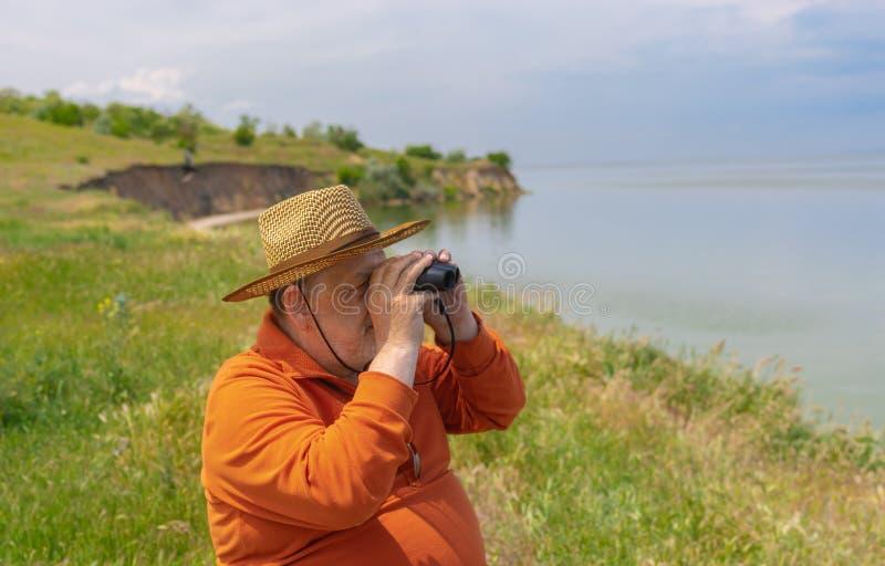 Hög man i sugrörhatten som ser in i binokulär stund som sitter på den Dnipro flodstranden royaltyfria foton