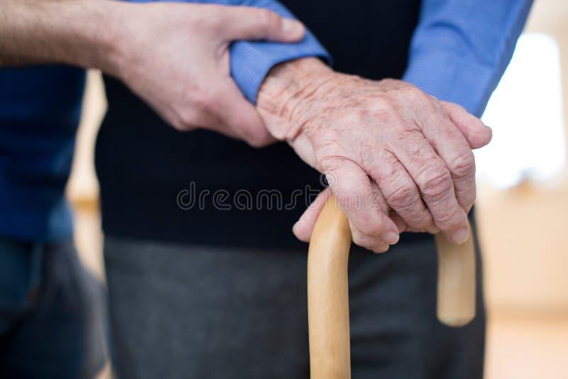Hög man med att gå pinnen som hjälps av omsorgarbetaren arkivbild