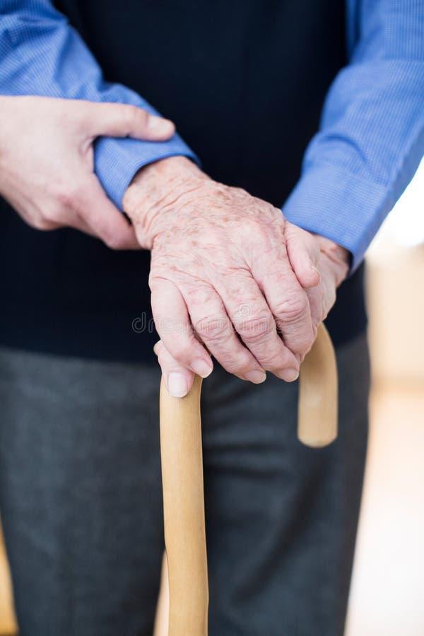 Hög man med att gå pinnen som hjälps av omsorgarbetaren royaltyfri bild