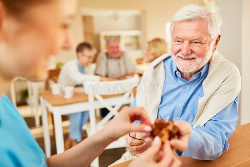 Hög man med demens och geriatrisk sjuksköterska royaltyfria bilder