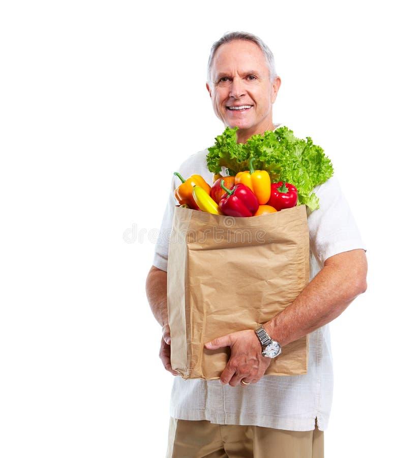 Hög man med en livsmedelsbutikshoppingpåse. royaltyfri foto