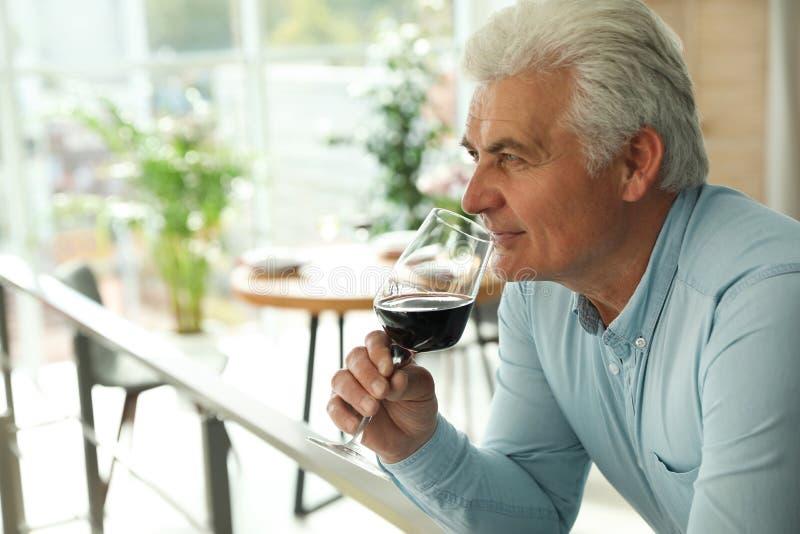Hög man med exponeringsglas av vin i restaurang arkivfoton