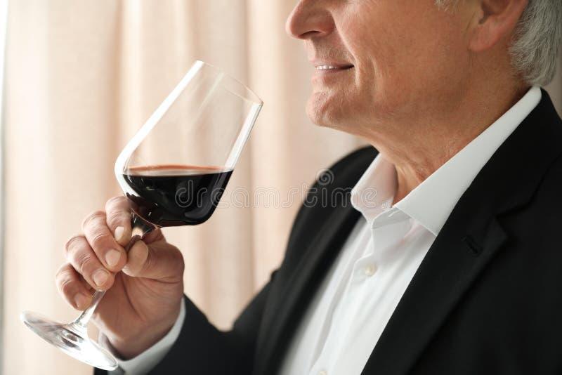 Hög man med exponeringsglas av vin inomhus royaltyfria foton