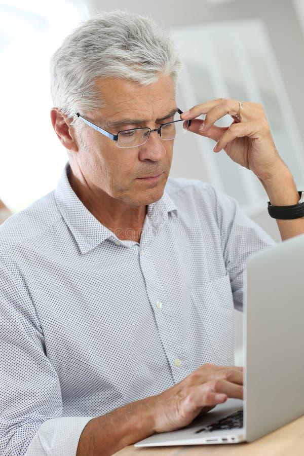 Hög man med glasögon genom att använda bärbara datorn royaltyfria foton
