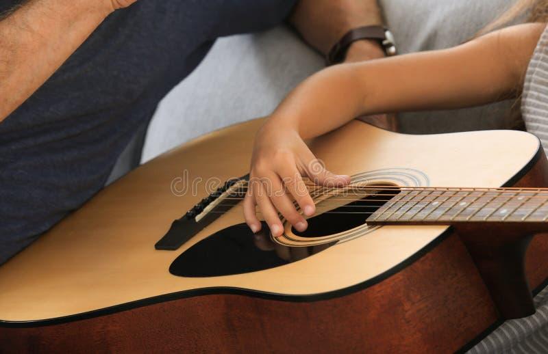Hög man med hans sondotter som hemma spelar gitarren royaltyfria foton